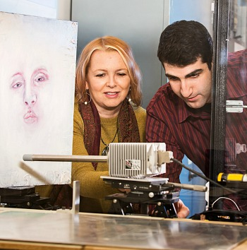 Fiona McNeill works with Eric Johnson on an x-ray focussing device designed to analyze elements in the paint used in Van Gogh's 'Ginger Jar with Onions.' This technique revealed a painting under the visible painting.