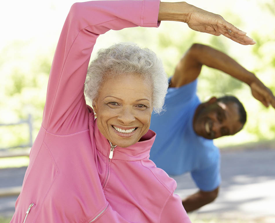 Senior African American couple stretching in the park