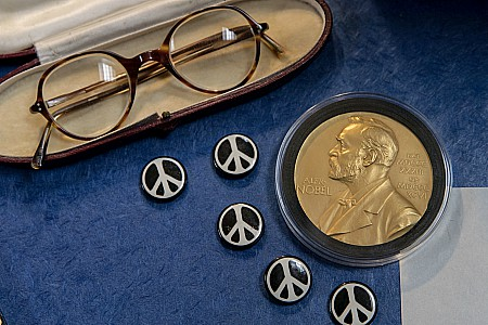 Items from the Russell Archives including his glasses, his Nobel medal, and buttons with the iconic peace sign, the symbol created by the Campaign for Nuclear Disarmament in which Russell was a central figure.