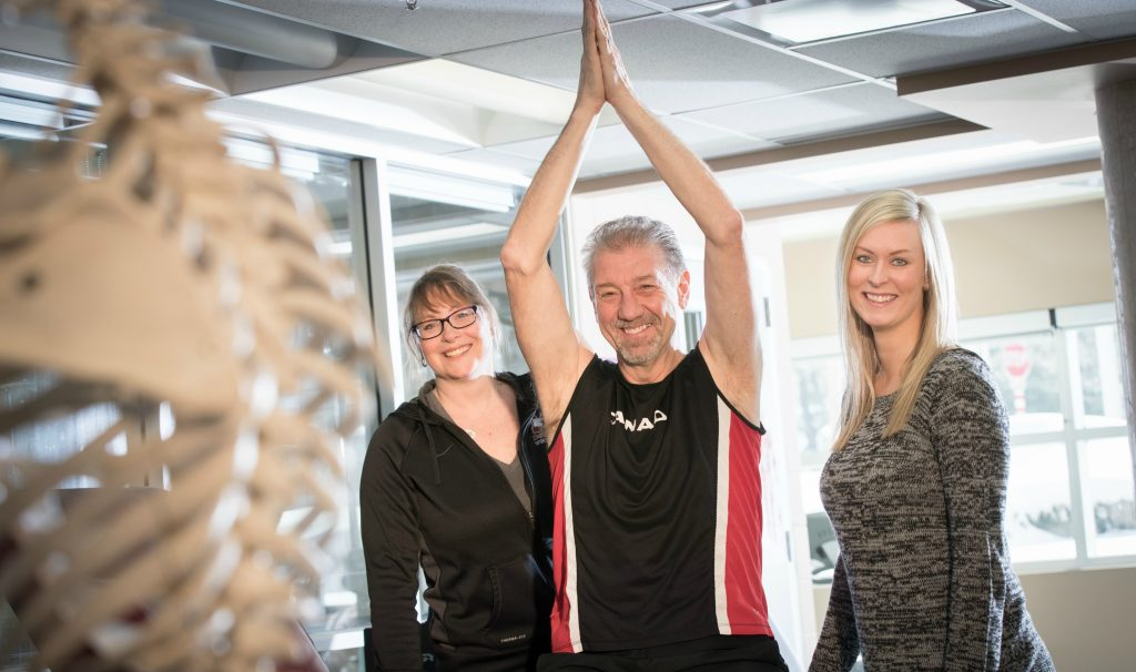 Steve Kalotinis proudly holds his arms above his head at the David Braley sport medicine clinic. Kalotinis worked closely with therapists at the clinic Sue Robinson, left, and Jillian Goodwin after having surgery on his shoulder.