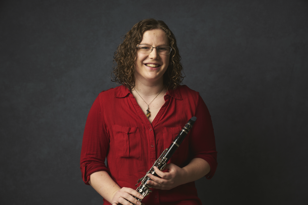 Photo of McMaster engineering student Larissa Taylor in a red shirt holding a clarinet