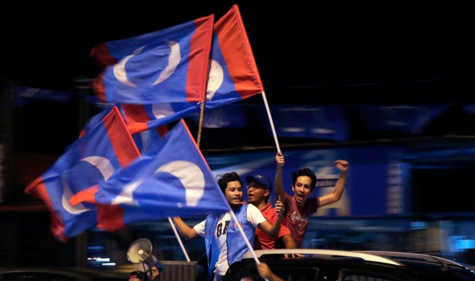 Supporters of Malaysia's opposition coalition party hold party flags in northern Malaysia on the eve of the country's recent election. Corruption-plagued Najib Razak was voted out while Mahathir Mohamad won. (AP Photo/Andy Wong)