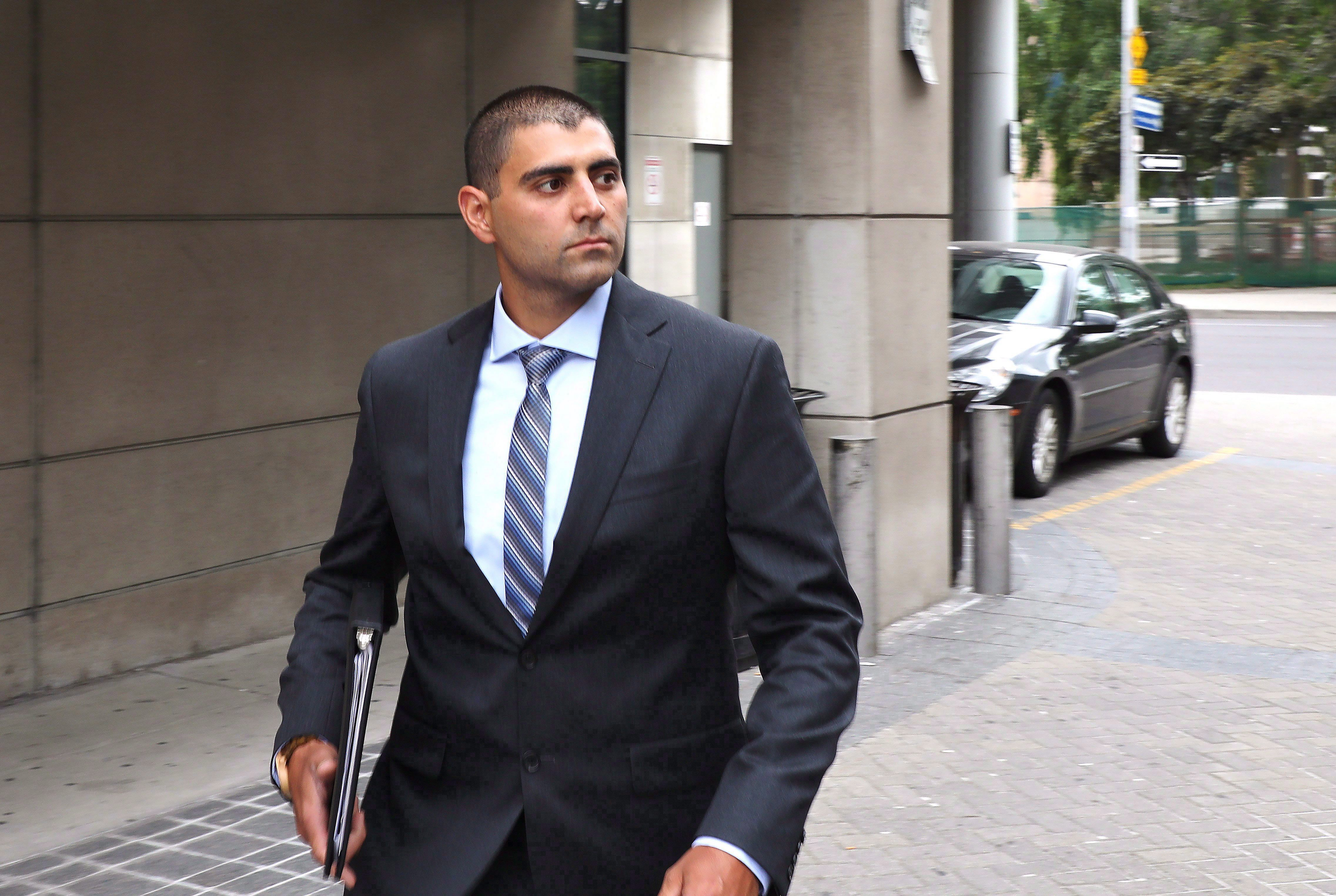 a mAN IN A BUSINESS SUIT STANDS OUTSIDE A COURTHOUSE