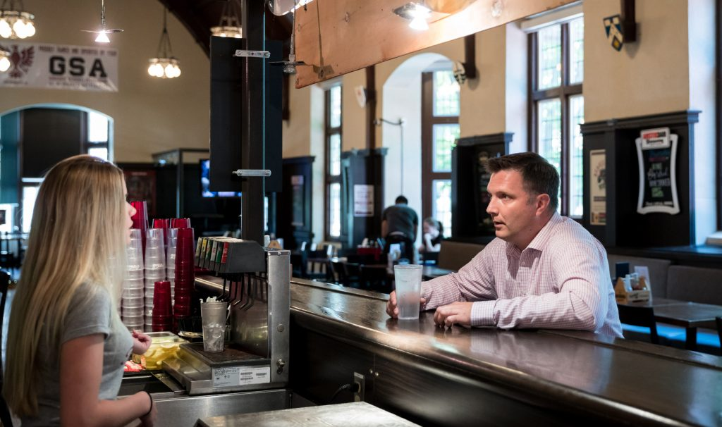 A bartender and a customer talk at a bar. The customer is Aaron Schat, a DeGroote School of Business associate professor who studies the way customers treat front-line service workers. Photo by Sarah Janes