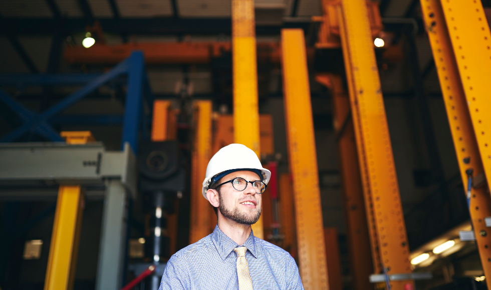A man with glasses and a hardhat stands in a building under construction