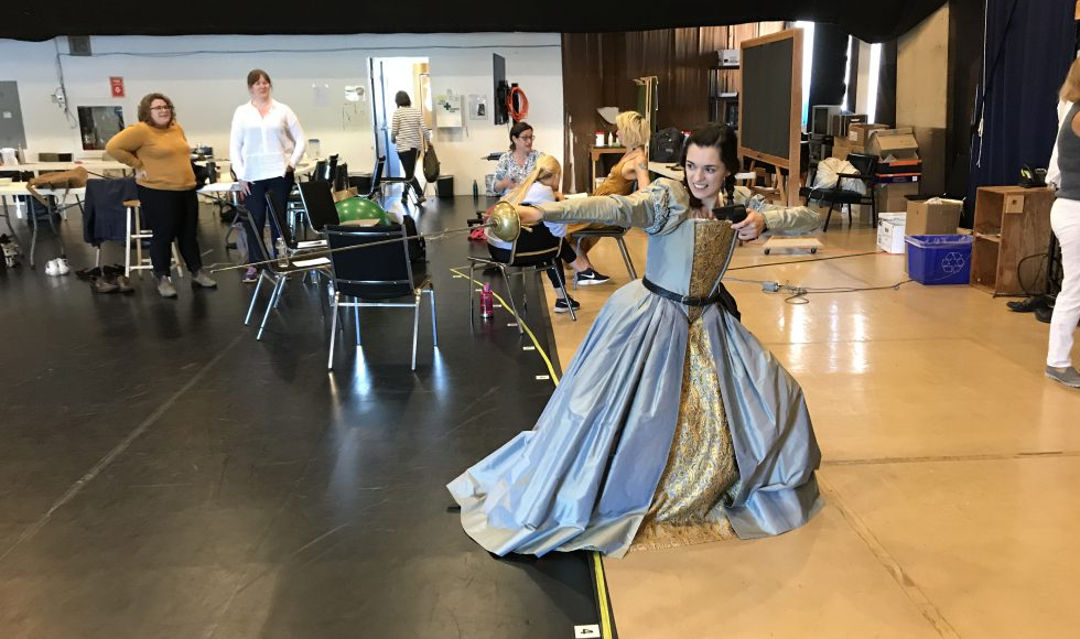 An actor in a blue dress lunges with a sword
