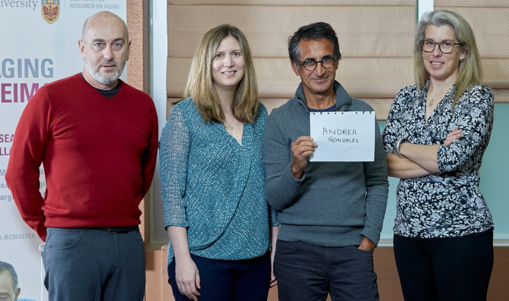 James Gillett, left, Marla Beauchamp, Parminder Raina and Brenda Vrkljan hold up the name of fellow researcher Andrea Gonzales after presenting their Catalyst grant-winning research proposals through the McMaster Institute for Research in Aging.