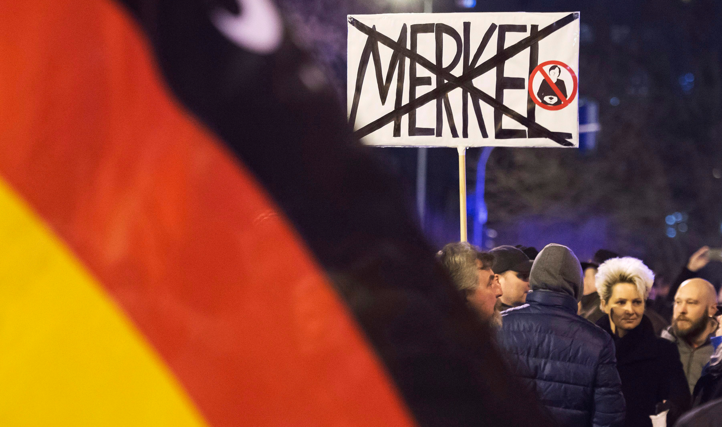 In this February 2016 photo, people wave German flags in Erfurt, central Germany, during a demonstration initiated by the Alternative for Germany (AfD) party. File photo by Jens Meyer/AP