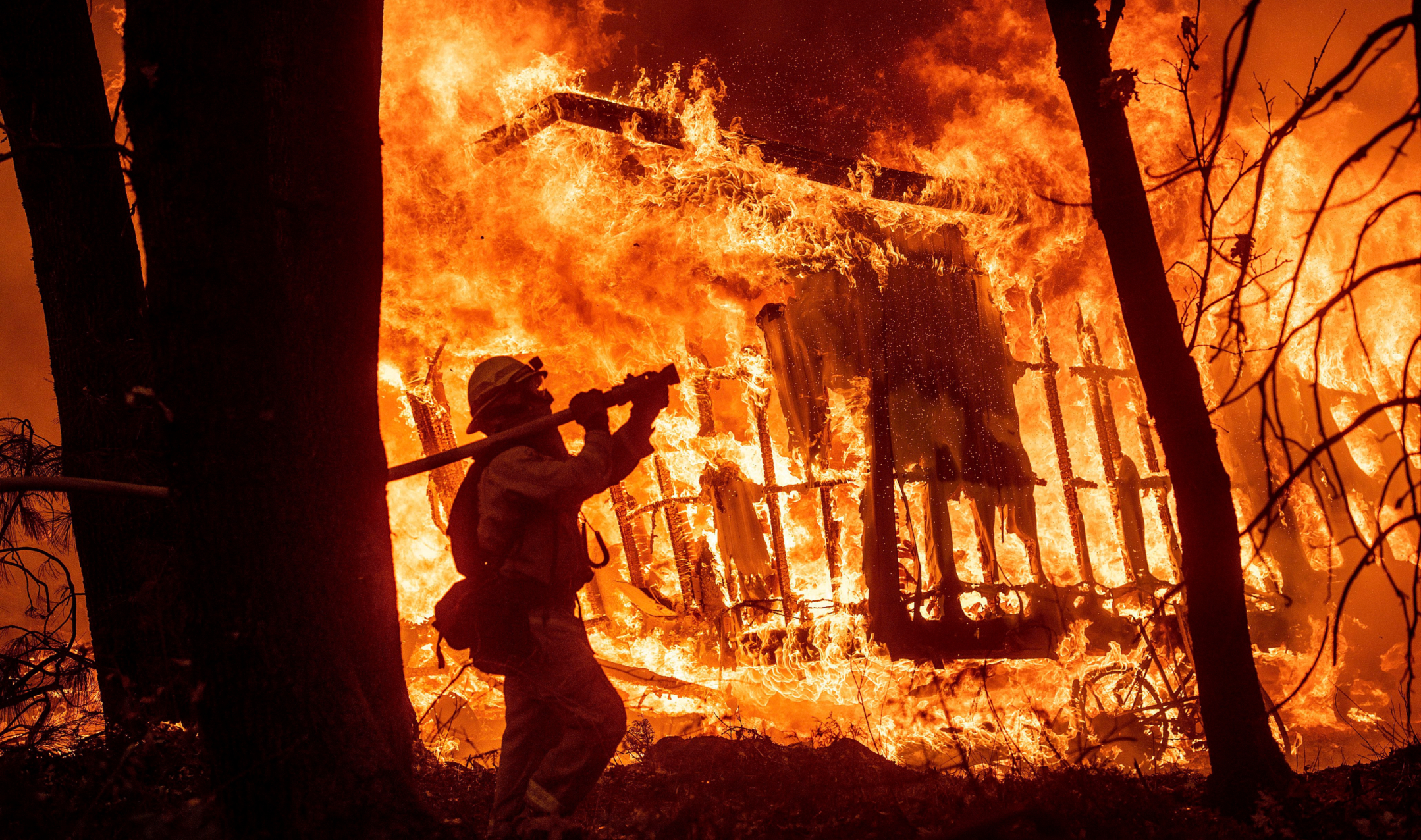Firefighter Jose Corona sprays water as flames from the Camp Fire consume a home in Magalia, Calif., on Nov. 9, 2018. Photo by Noah Berger/AP