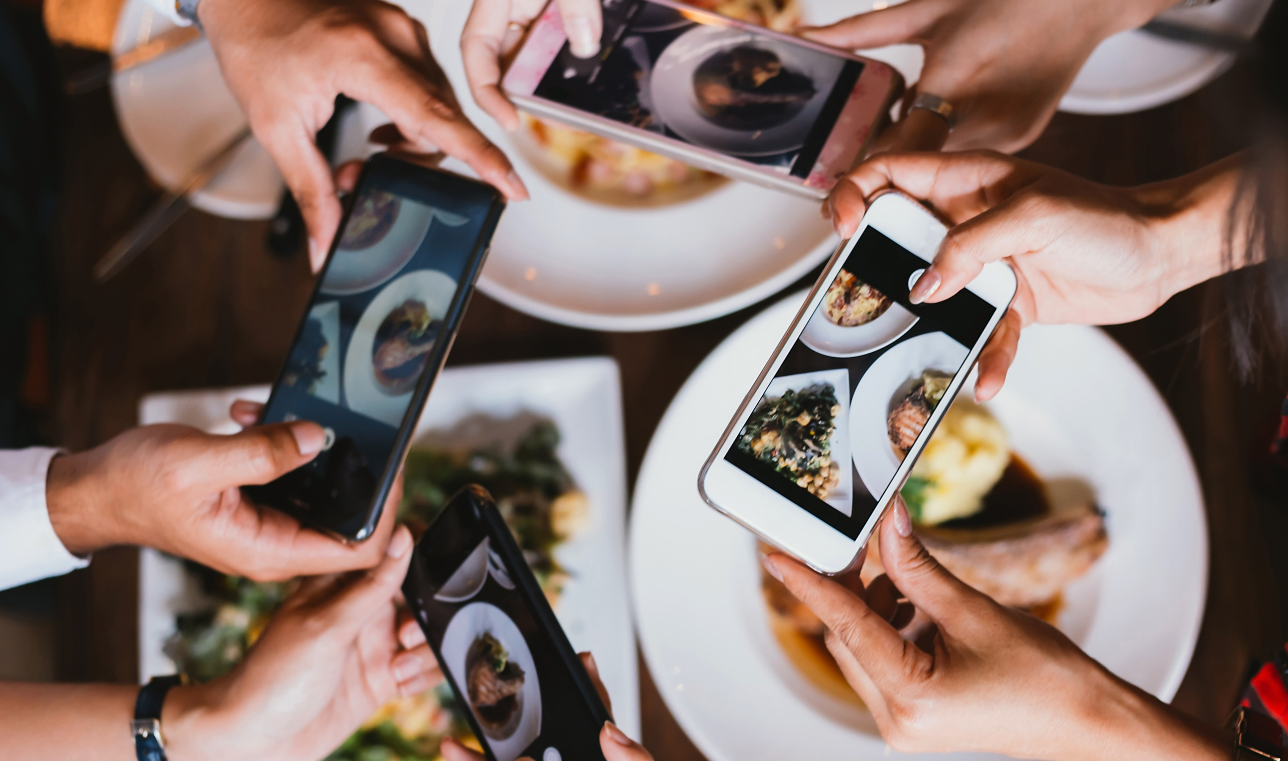 Many hands holding smartphones to take pictures of plates of food