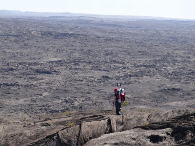 One researcher on a wide, rocky landscape