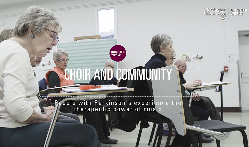 A group of older people sit in a music classroom singing