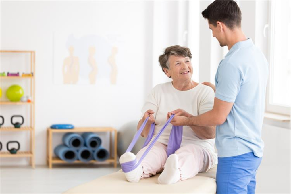 Stock photo of an older adult doing a leg stretch in a physiotherpy office with a physiotherapist