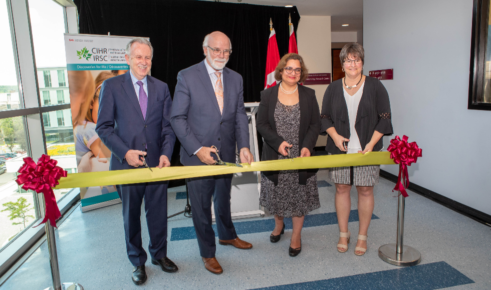 Two women and two men stand with scissors ready to mark the opening of the CIHR Institute for Infection and Immunity