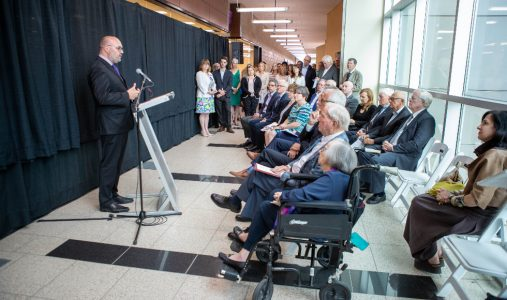 Dr. Gerry Wright standing at a podium in a hallway in front of a black curtain at the opening of the David Braley Centre for Antibiotic Discovery