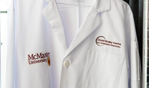 "Close-up of a lab coat that reads ""David Braley Centre for Antibiotic Discovery."""