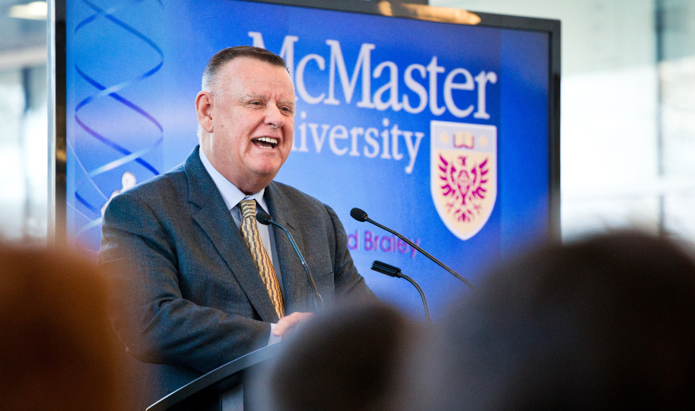A smiling man speaks at a lectern in front of a banner that says McMaster University