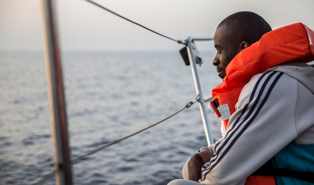 A man in a a lifejacket stares out to sea from on board boat. The NGO's boat is just outside Italian territorial waters off the coast of the island of Lampedusa, on July 4, 2019.