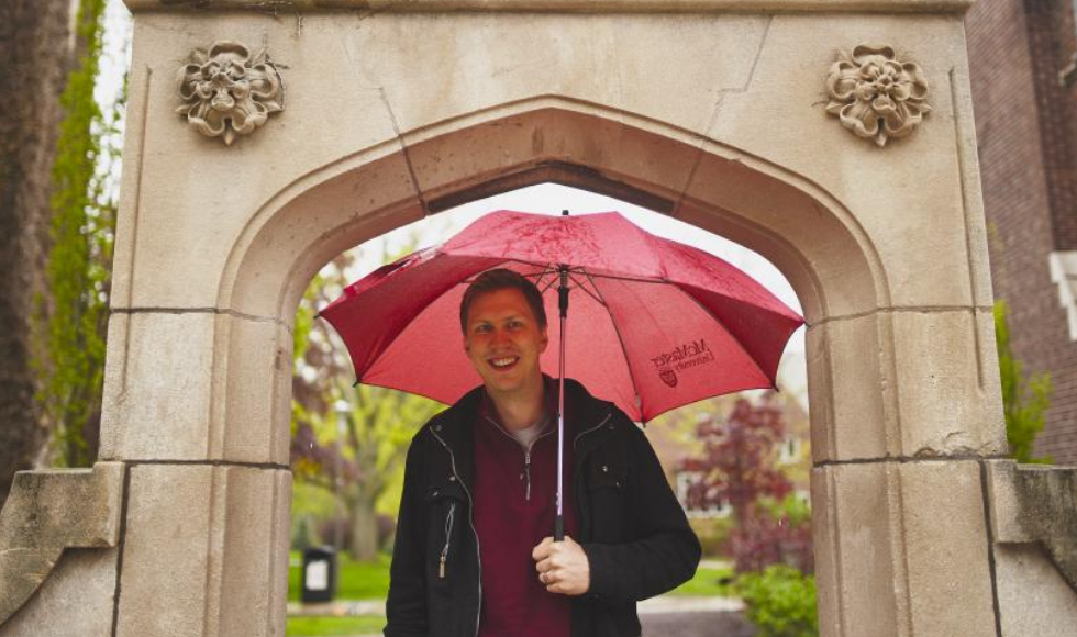 A man stands with a red umbrella under Edwards Arch at McMaster University