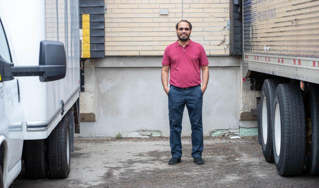 Elkafi Hassini standing in a loading area between two freight trucks.