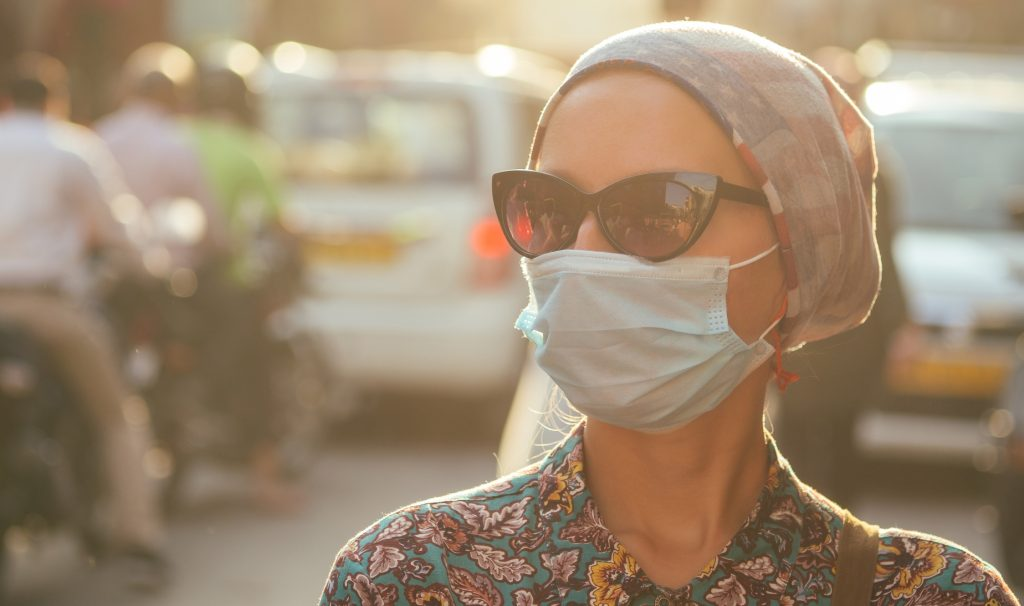 Stock image of women wearing a surgical mask outdoors