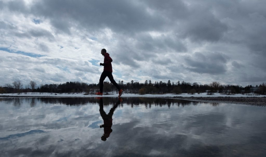 A jogger running solo past a big puddle that reflects them