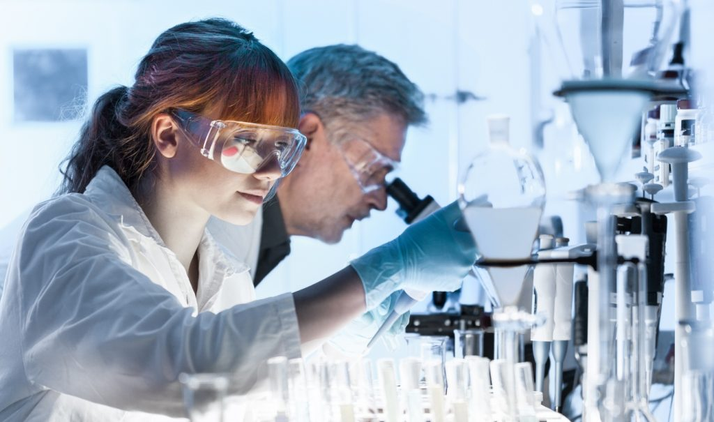 two scientists peering into microscopes