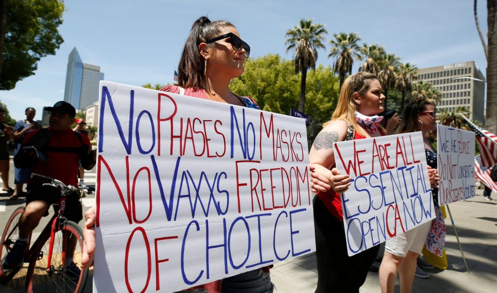 Protesters holding signs about vaccines and reopening at a protest in Sacramento.