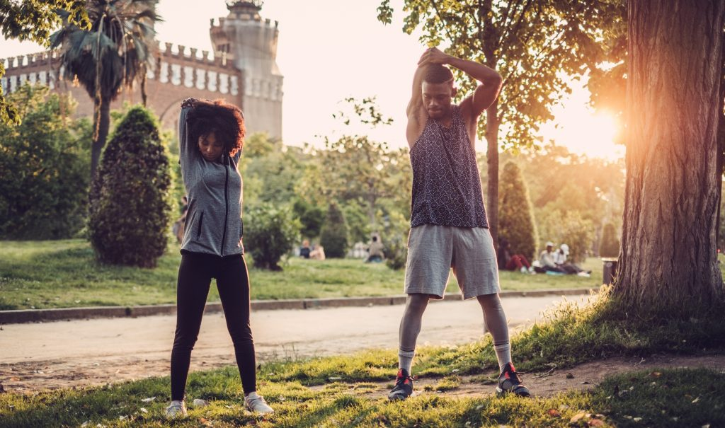 Two people stretching outdoors