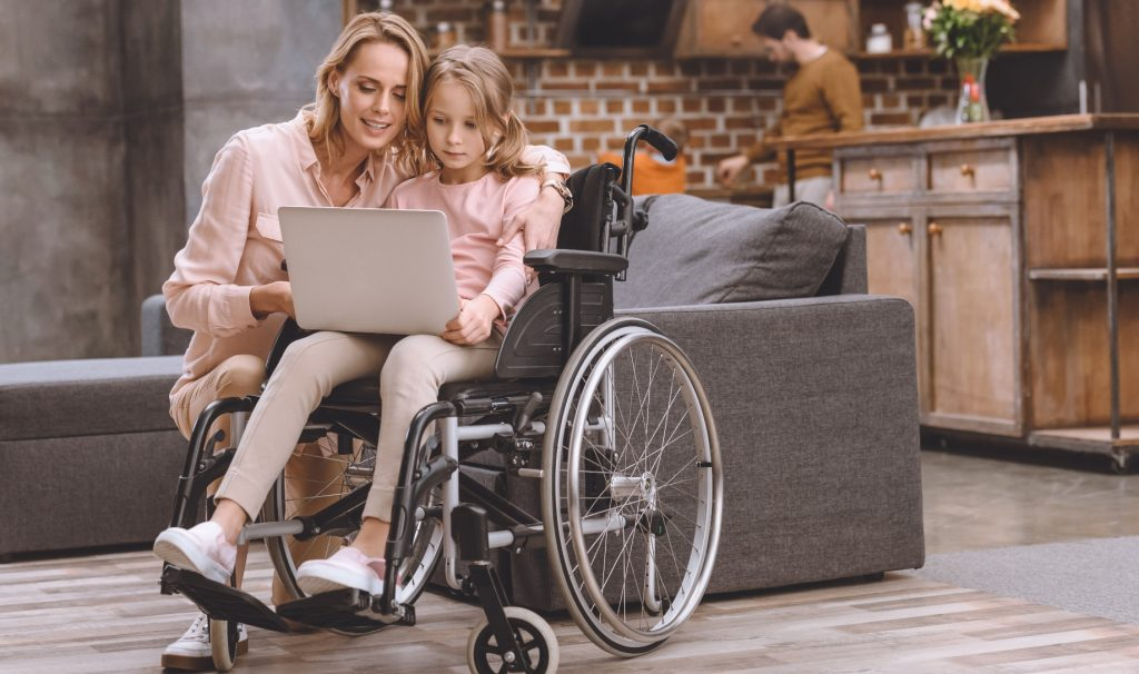 Woman crouching down beside little girl in a wheelchair. Both are looking at a laptop open on the girl's lap
