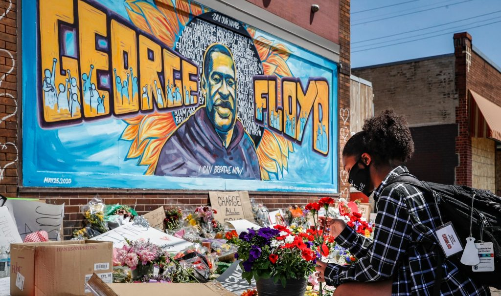 A person adds a bouquet to a growing pile of flowers beneath a painted mural of George Floyd