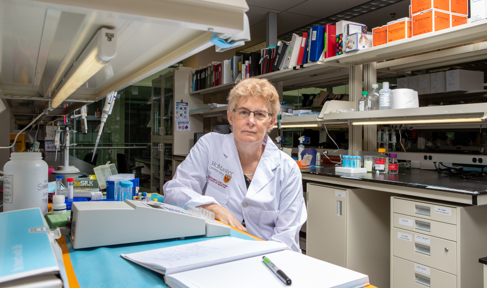 Photo of a woman in a lab coat, sitting at a lab table