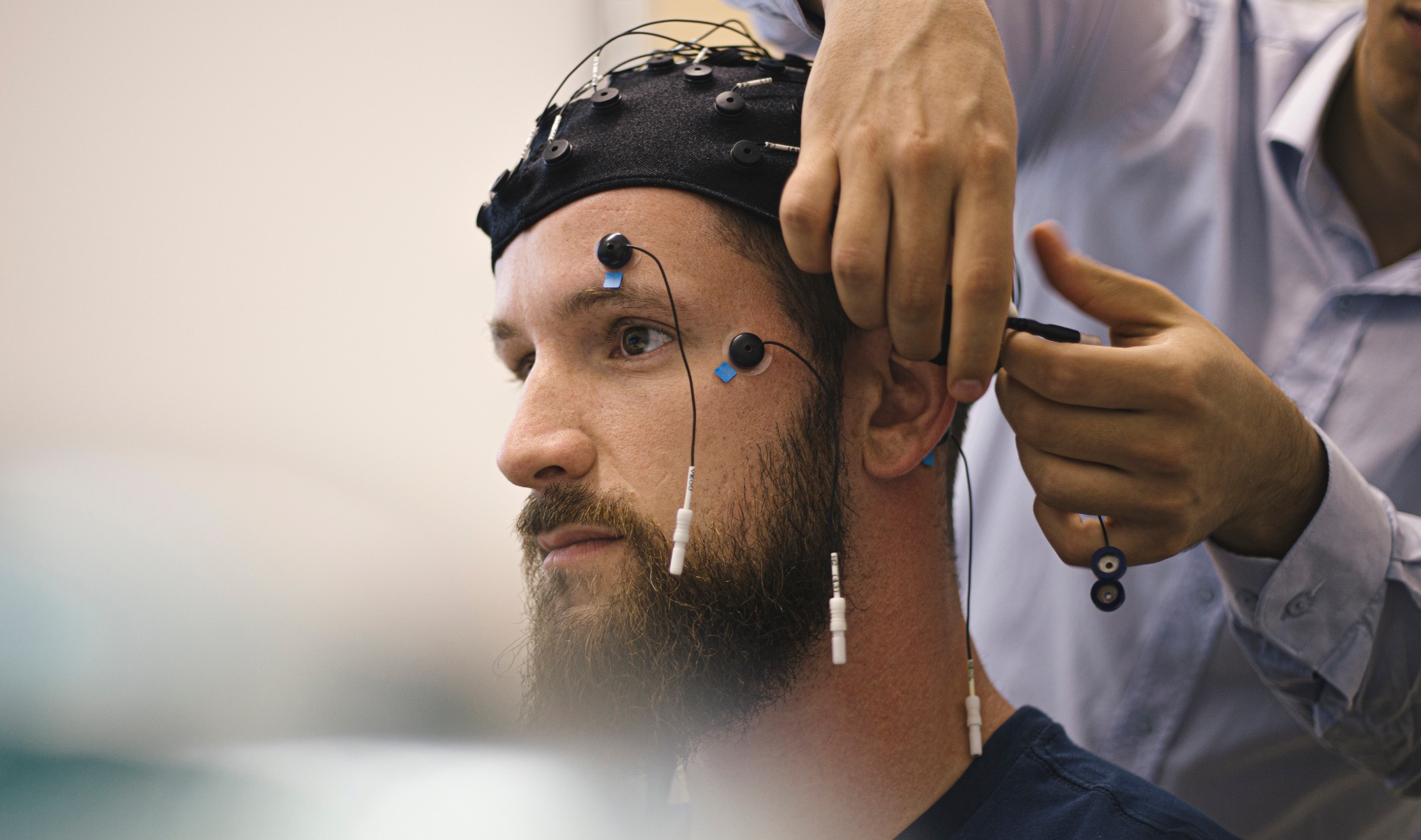 Closeup of a young, bearded man having electrodes hooked up to his head.