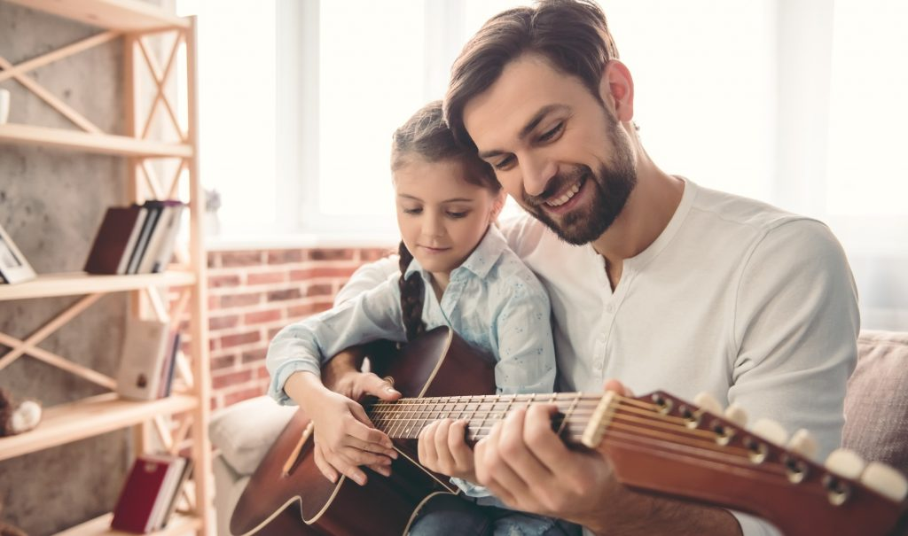 A smiling man is teaching a smiling little girl on his lap to play the guitar.