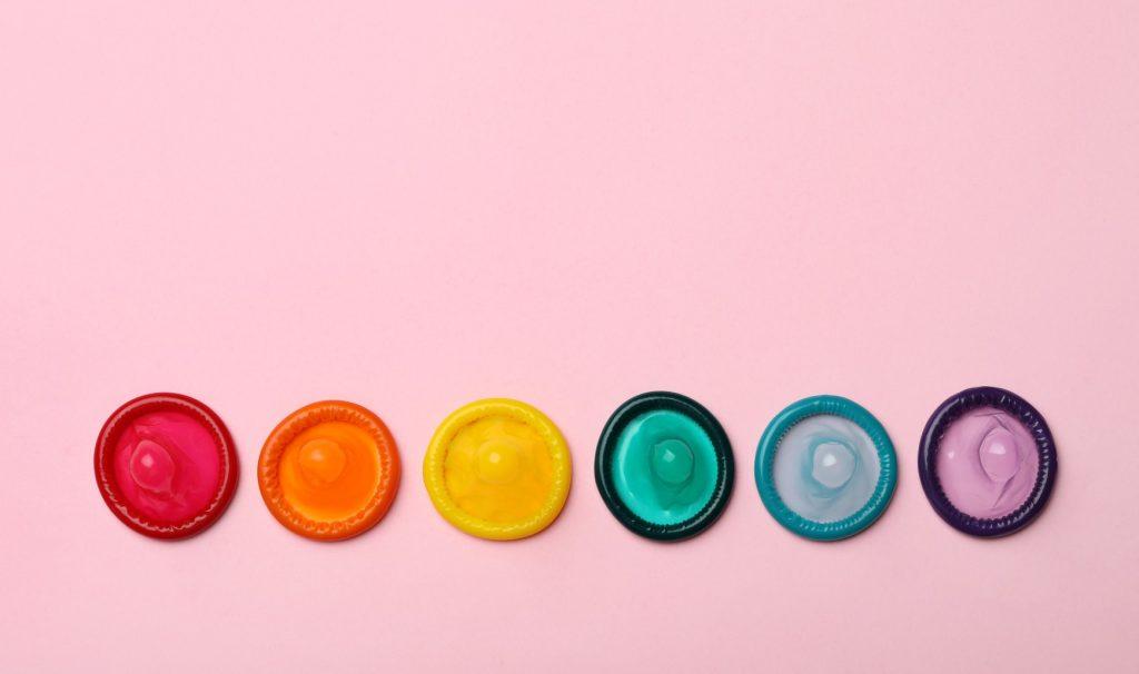 Coloured condoms arranged in a rainbow.