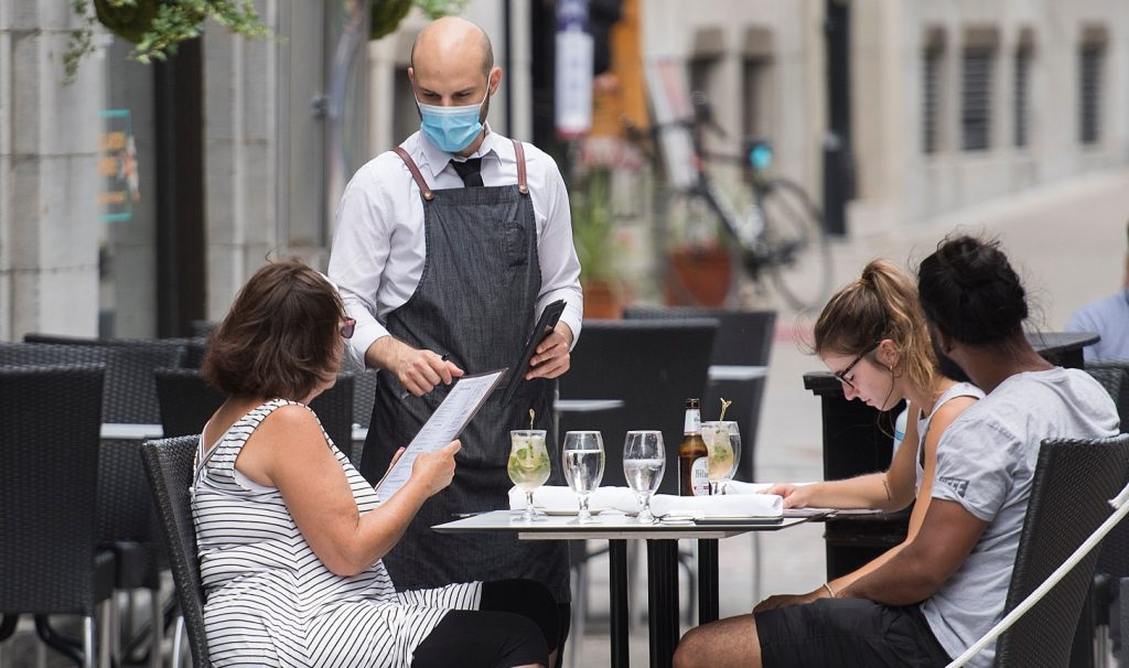 A server wearing a mask talks to a person holding a menu at a table on a patio alongside two others.