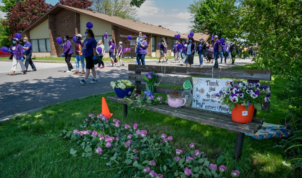 People march in support of nursing union members outside a retirement home.