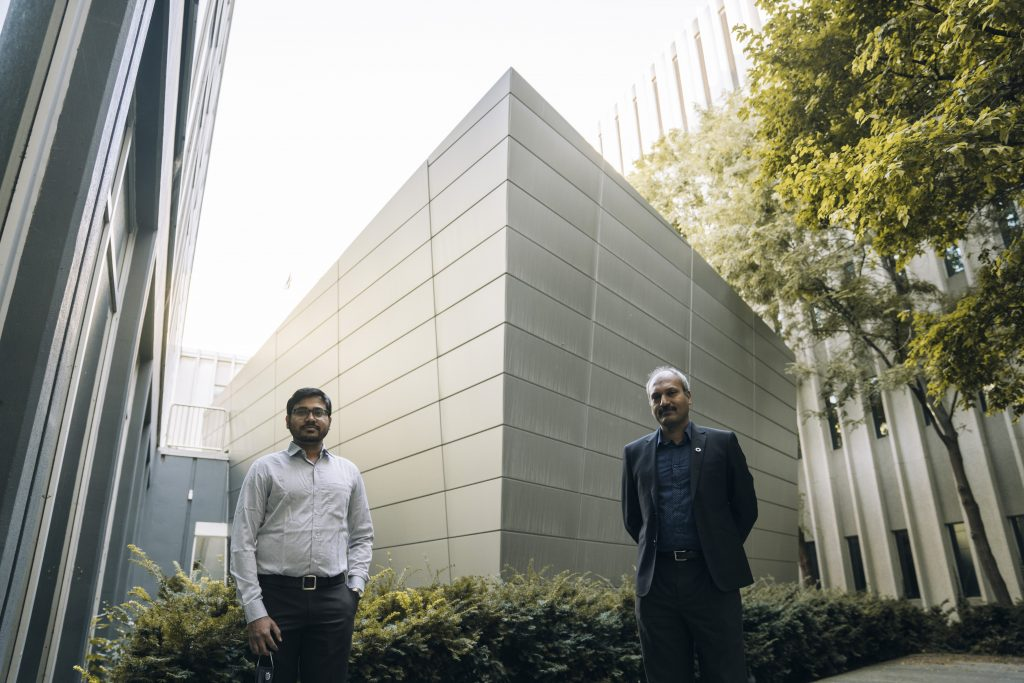 Smiling Rakesh Sahu and Ravi Selvaganapathy flank a building. They're standing six feet apart.