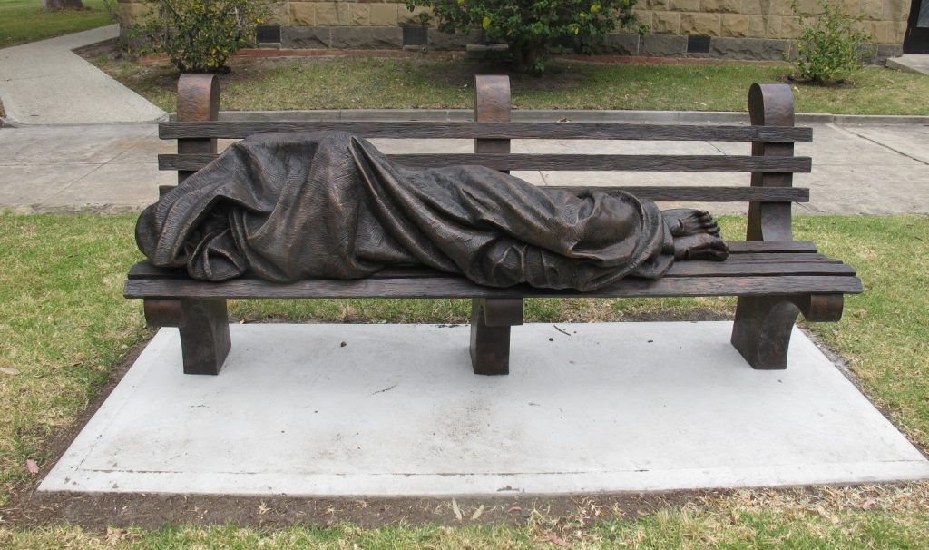 A dark bronze, realistic-looking statue of a person wrapped in a too-small blanket lying on a public bench.