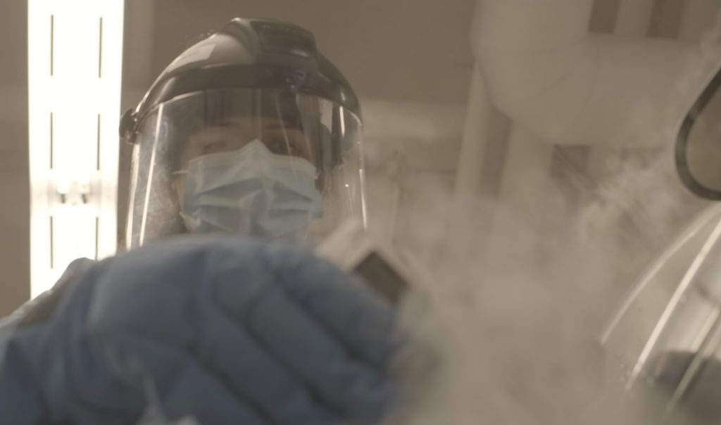 A scientist wearing full protective lab gear, including gloves, face shield, mask and gown, is carefully holding something with smoke or mist coming off it.