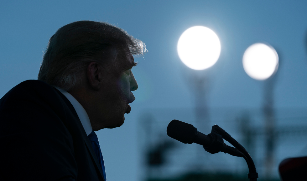 Donald Trump in close-up silhouette speaks into microphones
