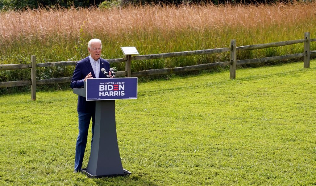 Joe Biden giving a speech from a podium in a grassy field in the sunshine.