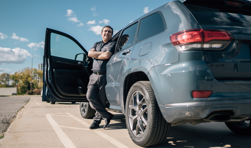 A smiling man stands outside in front of a minivan with its door open. The sky is blue and the sun is shining.