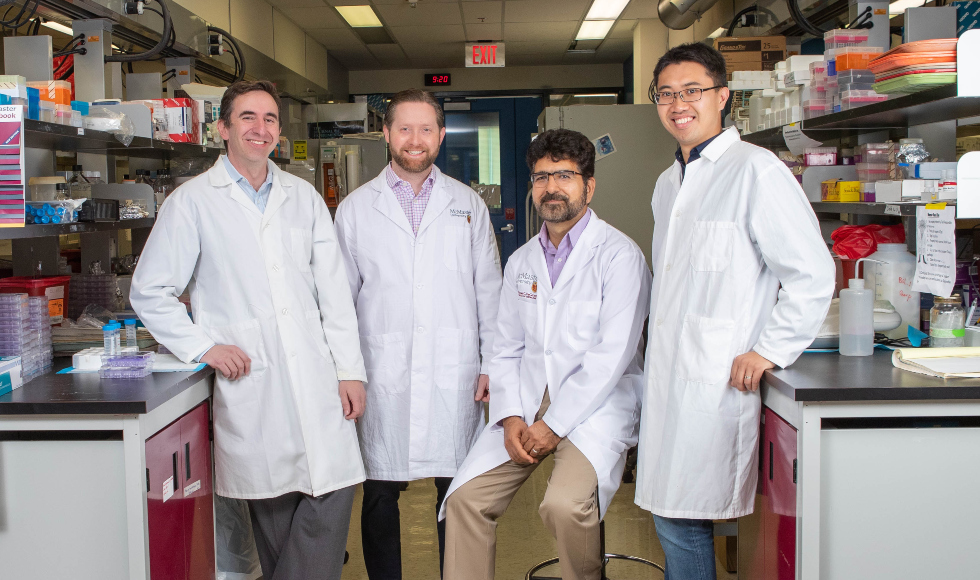 Four men in lab coats stand in a lab