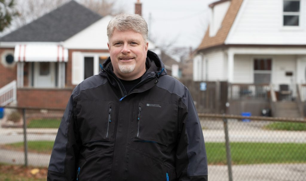 Jim Dunn is smiling at the camera in the foreground. Behind him are small houses on a residential city street.
