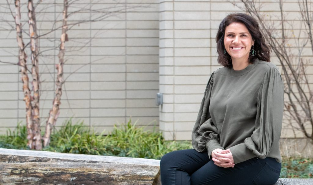 Vanessa Watts sitting on a log bench outside a building, smiling.