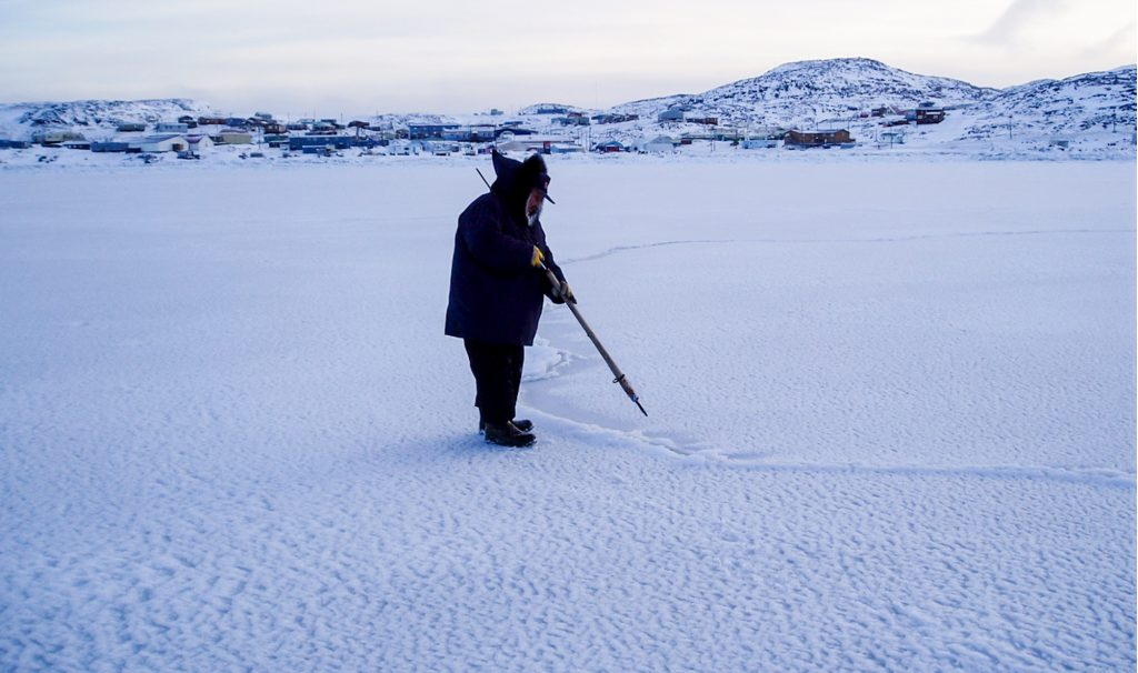 A figure in a parka stands on snow-covered sea ice in the foreground, testing it with a pointy object. Far on the other side of the ice in the background, a lot of low, snow-covered buildings.