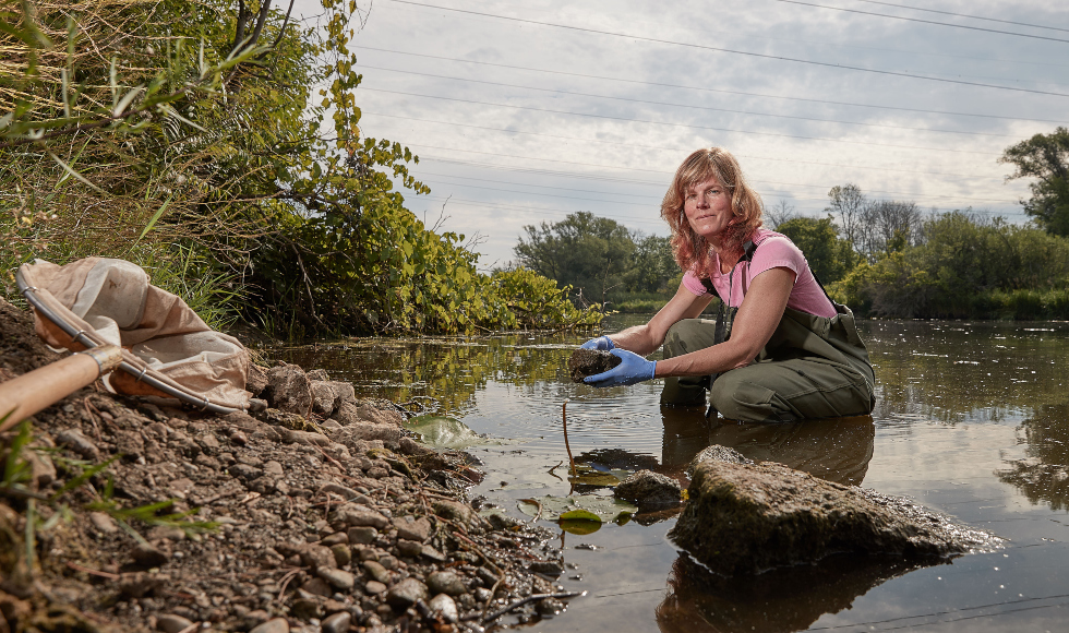 A woman wearing hip-waders crouches in shallow water, holding a clump of dirt