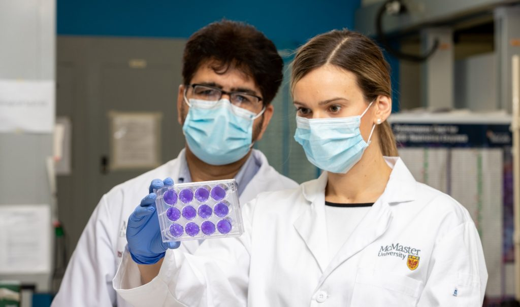 Sophie Poznanski holds up samples in a lab and she and Ali Ashkar —both masked —are looking at them.