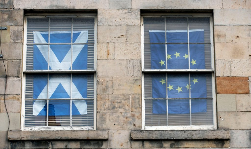 Two apartment windows, side by side: one is curtained by a Scottish Saltire flag, the other by an EU flag.